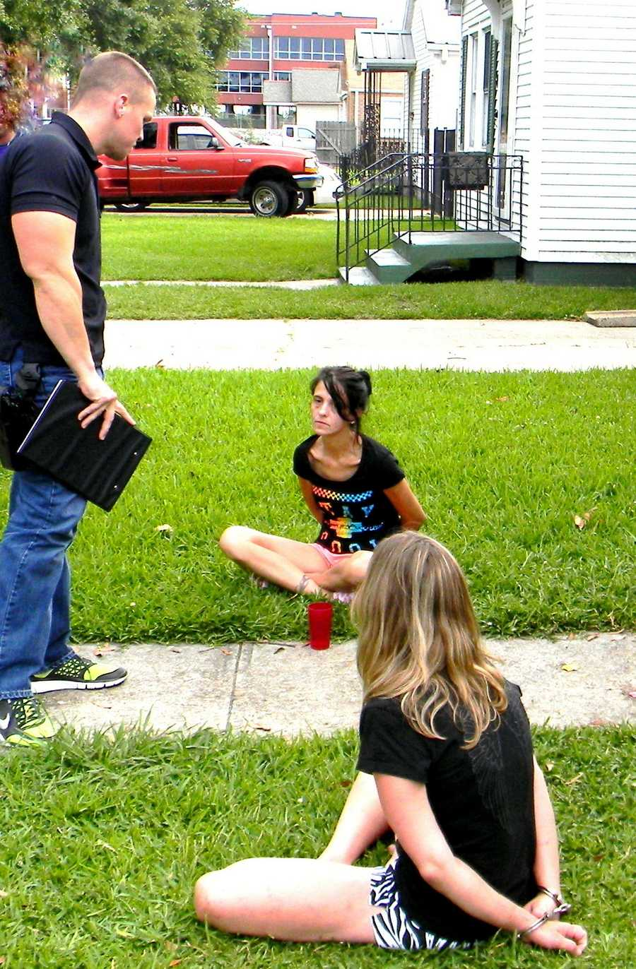 Narcotics Agent Daniel Bostic talks with the suspects on the ground, Rachel Butler in the foreground and Melissa Huy in the background.