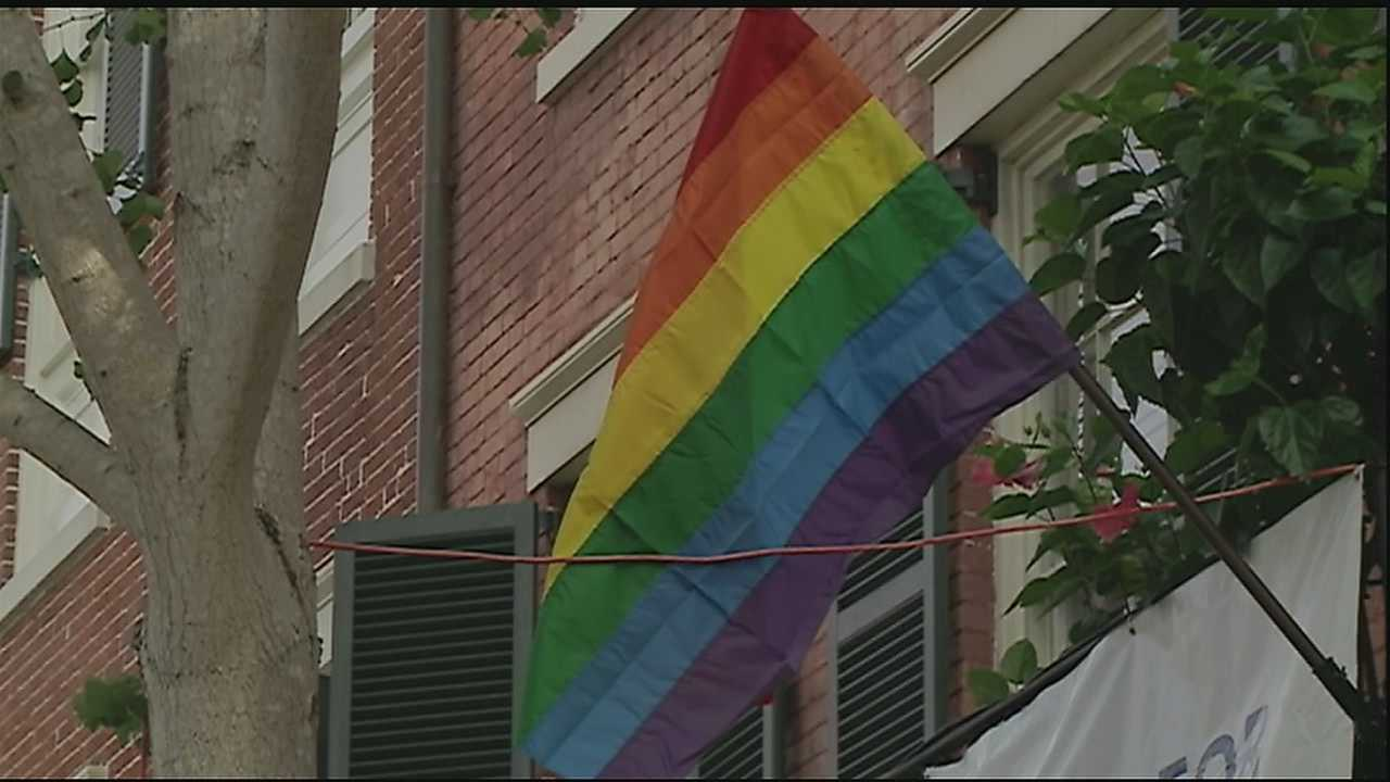 A man is caught on surveillance video tearing down a gay pride flag and spray painting a derogatory term on the building's shutters.