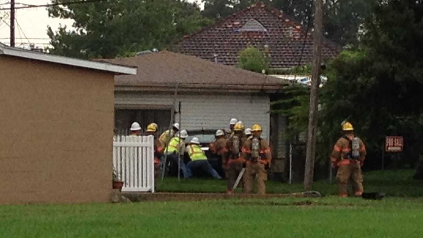 Authorities in Jefferson Parish work to remove a car that apparently crashed into a Metairie home.