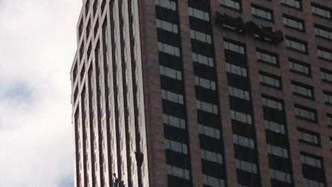 A worker awaits rescue from a failed window washing platform on a Central Business District high rise.