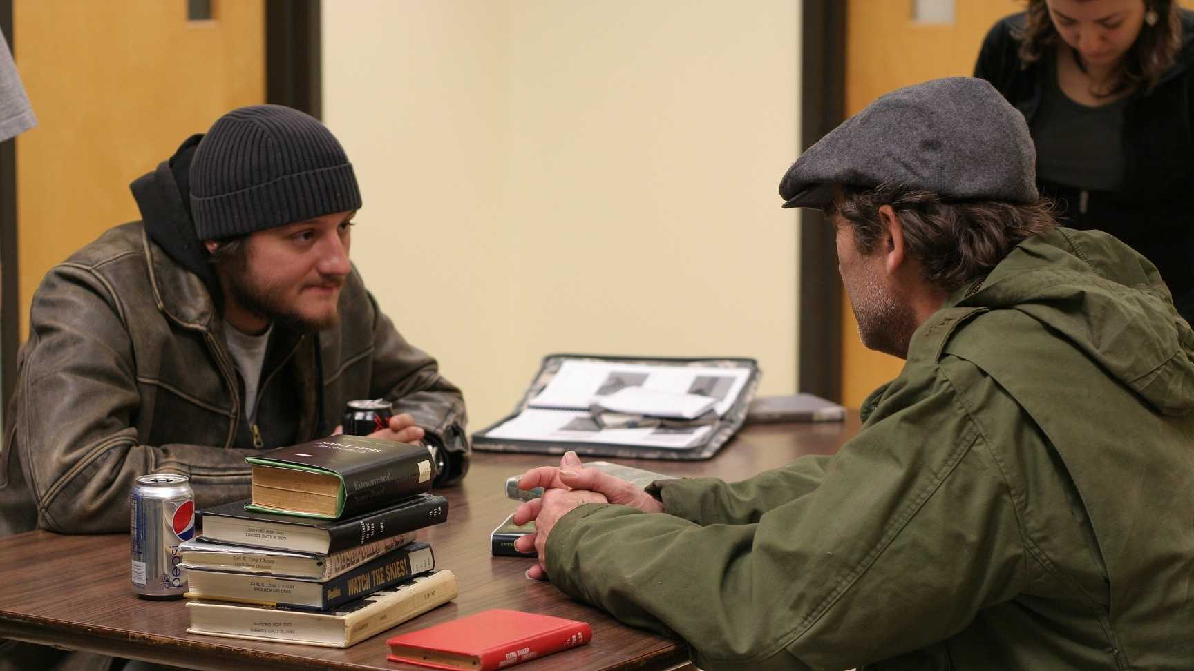 "Director James Roe (left) talks to actor Tracy Miller on the set of the film ""AM800."" This scene was shot in UNO's Earl K. Long Library."