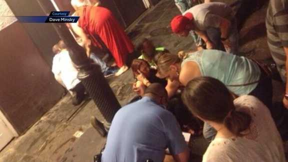 Police and bystanders assist Amy Matthews after she was shot in the mouth on Bourbon Street on Sunday morning.