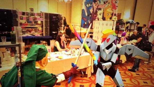 "A photo of Link from ""The Legend of Zelda"" series clashes swords with Laura Ducros, who is clad in an armored version of Rainbow Dash."