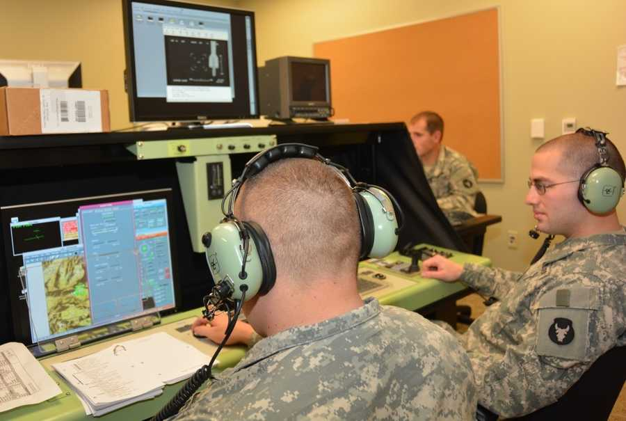 Two Soldiers from the Iowa National Guard – SSG Andrew Willems of Polk City, Iowa, and SPC Andrew Hensen of Pall, Iowa – train on the Unmanned Aerial Vehicle (UAV) flight simulator at the Louisiana National Guard's new Tactical Unmanned Aircraft Systems Operations Facility at Fort Polk in Leesville, Louisiana, on Jan. 13, 2015. TUASOF consists of nearly 10,000 square feet&#x3B; it sits on 11.5 acres and includes a 1,200 foot UAS runway.