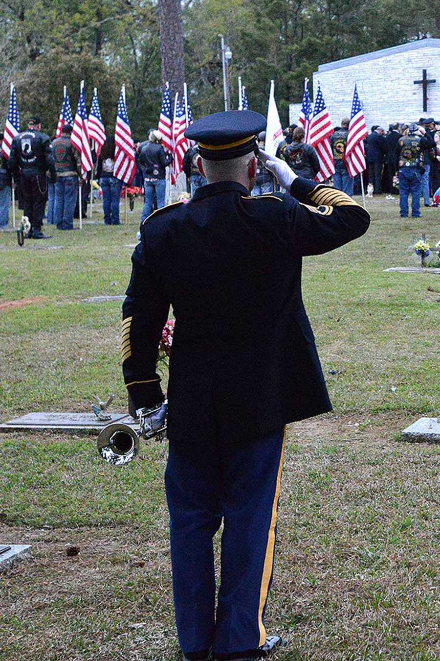 The bugler for the Louisiana National Guards salutes to honor fallen Soldier Chief Warrant Officer 4 George David Strother at Alexandria Memorial Gardens in Alexandria, La.