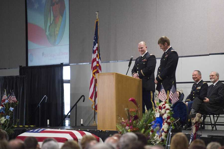 Capt. Michael Permenter (left) and Chief Warrant Officer 2 Jesse Futrell (right) recount humorous stories involving fallen Soldier Chief Warrant Officer 4 George David Strother before a packed audience of family and friends at the Alexandria Riverfront Convention Center in Alexandria, La. Strother was killed along with three other Guardsmen and seven Marines in a UH-60M Black Hawk crash in the Santa Rosa Sound, Navarre, Florida, March 10.
