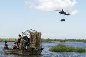 A Louisiana National Guard UH-60 Black Hawk helicopter from the 1st Assault Helicopter Battalion, 244th Aviation Regiment lowers a bundle of recycled Christmas trees into Bayou Sauvage during the annual Christmas Tree Drop in New Orleans.