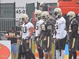 Saints players stand and watch before the beginning of practice.