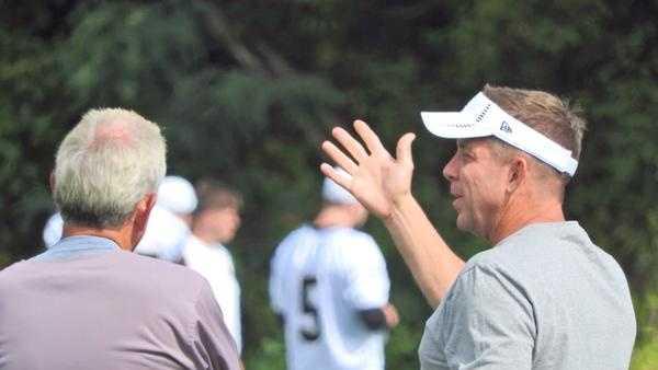Coaches Sean Payton and Joe Vitt talking before team drills.