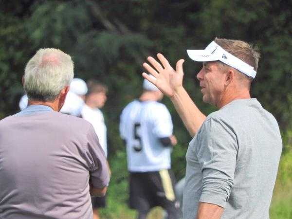 Coaches Sean Payton and Joe Vitt talking before team drills.