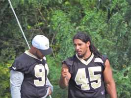 Linebackers Kasim Edebali and Hau'oli Kikaha talking before defensive drills.