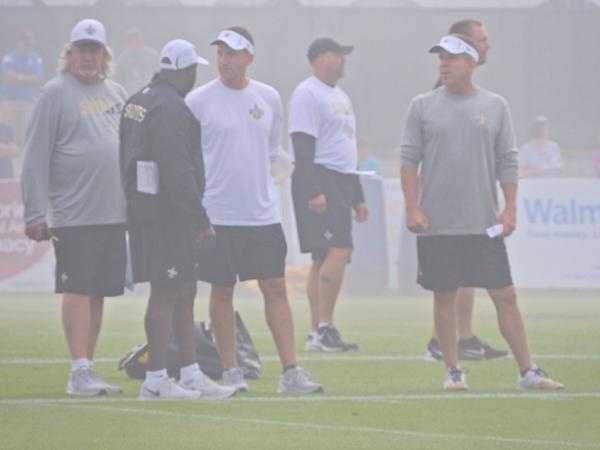 Saints coaches Sean Payton, Rob Ryan, and Dennis Allen talking during team drills.
