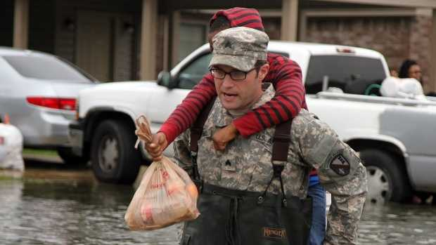Sgt. Jason C. Carroll, electronic warfare specialist with the Louisiana National Guard's 528th Engineer Battalion, 225th Engineer Brigade, carries a young resident through flooded streets in Monroe, Louisiana, March 10, 2016. The 528th used high-water vehicles, in cooperation with the Ouachita Parish Sheriff's Office, to navigate high waters to assist evacuating residents.