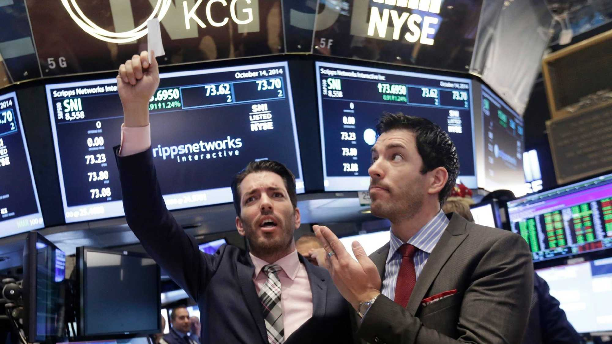 "In this Oct. 14, 2014, file photo, Jonathan Scott, left, and Drew Scott, of HGTV's ""Property Brothers"" cable television show, mimic traders on the floor of the New York Stock Exchange.AP Photo/Richard Drew, File"
