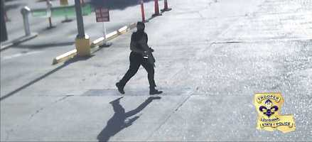 Accused Baton Rouge shooter Gavin Long running with a weapon and dressed in black.