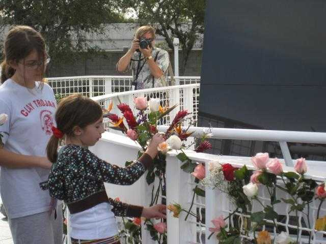 Before and after the ceremony, many members of the crowd attached flowers to the railing in front of the Memorial.