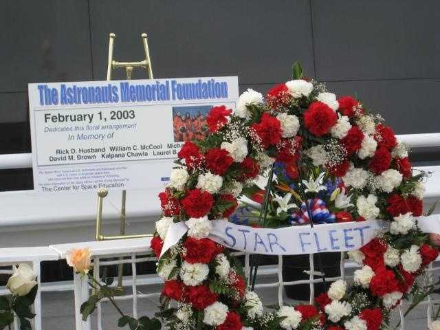 A wreath and sign at the bottom of the wall pay tribute to the fallen astronauts.