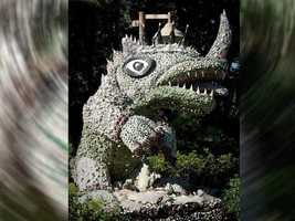 """If you guessed the dinosaur sculpture at the Dinoland U.S.A. area of Disney's Animal Kingdom park then you are right! Called the """"Party 'O Saurus,"""" it was sculpted by a folk artist known as Mr. Imagination. Look close, there's a special pin embedded in the sculpture."""