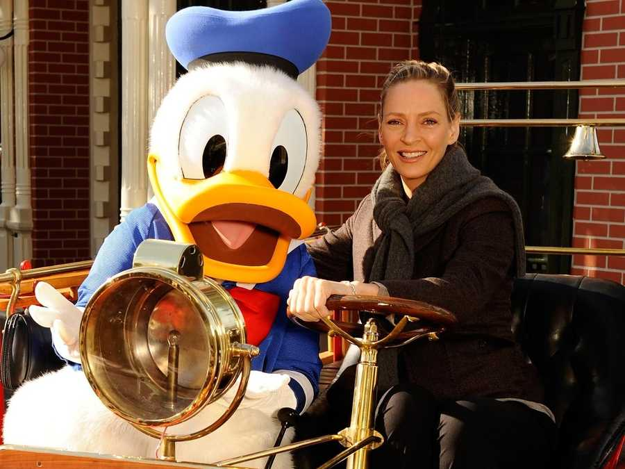 Actress/model Uma Thurman poses Jan. 14, 2012 with Donald Duck in a 1900s-inspired fire engine while visiting the Magic Kingdom park at Walt Disney World in Lake Buena Vista, Fla.