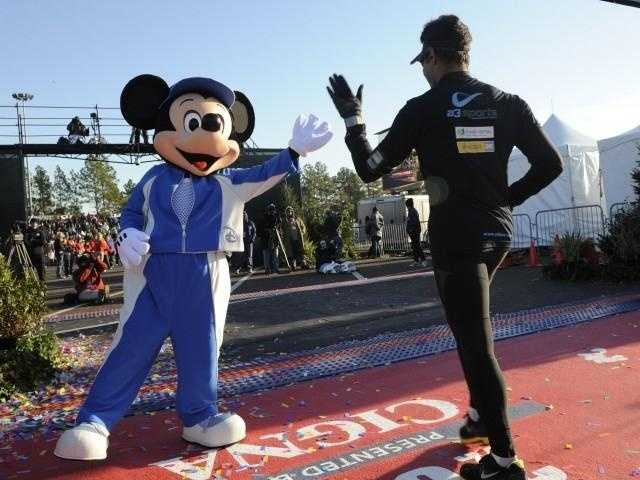 He's been around for years and he's never looked better, so he must be a fan of fitness. Wearing a blue track suit, Mickey high-fives runners at the finish line of the Walt Disney World Marathon.