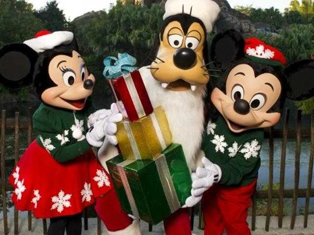 Who says holiday sweaters aren't fashionable? Mickey, Minnie and pal Goofy pull them off well.