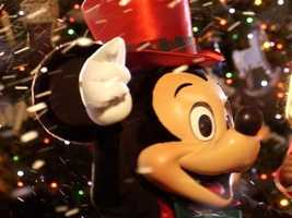 Mickey welcomes guests to his Very Merry Christmas party wearing a red top hat.