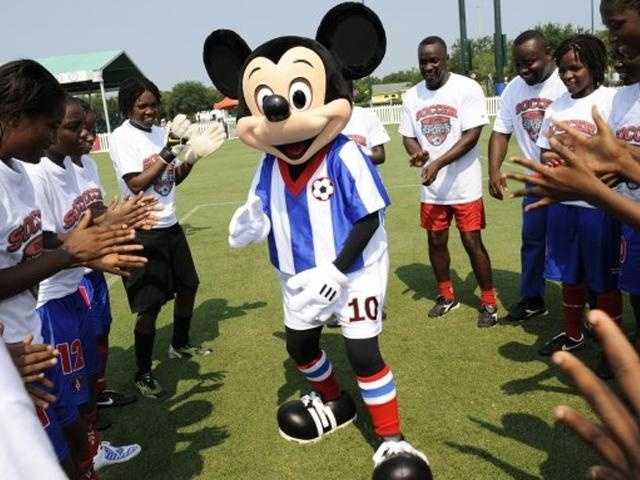 Mickey sports a soccer outfit and dances for the Haitian women's league.