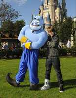 "Justin Bieber poses Dec. 19, 2009 with the ""Genie"" from Disney's animated film ""Aladdin"" at the Magic Kingdom in Lake Buena Vista, Fla. Bieber was in central Florida to perform at a Radio Disney concert at the Celebration Town Center in nearby Celebration, Fla."