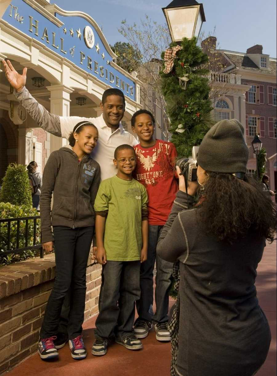 """Actor/author Blair Underwood, who portrays U.S. President Elias Martinez on the NBC series """"The Event,"""" poses Dec. 29, 2010 in front of """"The Hall of Presidents"""" attraction at the Magic Kingdom in Lake Buena Vista, Fla., as his wife Desiree (foreground) takes a photo of him and their children (L-R): daughter Brielle, son Blake and their oldest son, Paris."""