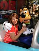 "Emmy Award-winning actress, writer & producer Tina Fey, star of the hit feature film ""Date Night"" and executive producer, head writer and star of the NBC series ""30 Rock,"" poses April 23, 2010 with Goofy at the Sci-Fi Dine-In Theater restaurant at Disney's Hollywood Studios theme park in Lake Buena Vista, Fla. Fey was visiting Walt Disney World Resort on vacation with her family."