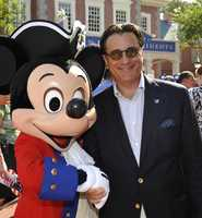 Actor Andy Garcia poses with Mickey Mouse July 3, 2009 at the Magic Kingdom in Lake Buena Vista, Fla. Garcia was the keynote speaker at an in-park ceremony in which more than 1,000 immigrants from 100 countries became new U.S. citizens. Garcia -– a naturalized citizen himself -- spoke to the new citizens in front of the park's Cinderella Castle.