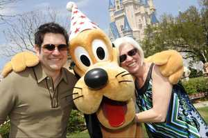 "Jay DeMarcus (left) of the country music trio ""Rascal Flatts,"" and his mother Caron Myers (right) pose April 9, 2010 with Pluto in front of Cinderella Castle at the Magic Kingdom in Lake Buena Vista, Fla. DeMarcus took his mother to Walt Disney World to celebrate her 60th birthday."