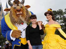 """Singer and former """"American Idol"""" champion Kelly Clarkson poses with Princess Belle (right) and Beast (left) from Disney's """"Beauty and the Beast"""" Feb. 19, 2012 in the Rose Garden area of the Magic Kingdom theme park at Walt Disney World Resort."""