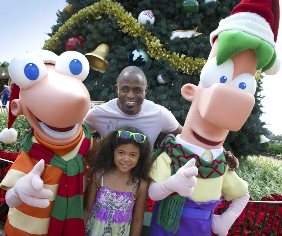"Emmy Award-winning entertainer Wayne Brady and his daughter, Maile, pose with Disney's ""Phineas & Ferb"" characters in front of the holiday tree at Epcot theme park at Walt Disney World Resort in Lake Buena Vista, Fla."