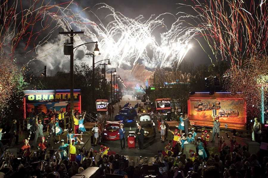 Confetti cascades while rows of bright neon signs, illuminated billboards and pyrotechnics light up the night as dozens of costumed performers and Disney executives celebrate the gala opening of Cars Land at Disney California Adventure park at Disneyland Resort in Anaheim, Calif.