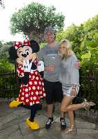 """In a photo taken July 24, 2012, five-time Grammy Award-winning singer Carrie Underwood and her husband, NHL star Mike Fisher of the Nashville Predators, pose with Minnie Mouse at Disney's Animal Kingdom park in Lake Buena Vista, Fla. Underwood and Fisher took a vacation with friends to Walt Disney World Resort before she continues preparation for her upcoming concert tour of North America, """"The Blown Away Tour,"""" in support of her latest number one album, """"Blown Away."""""""