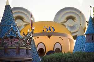 A couple of days before Disneyland's 50th anniversary, the Happiest Balloon on Earth made an appearance behind Sleeping Beauty's Castle as it was being inflated.