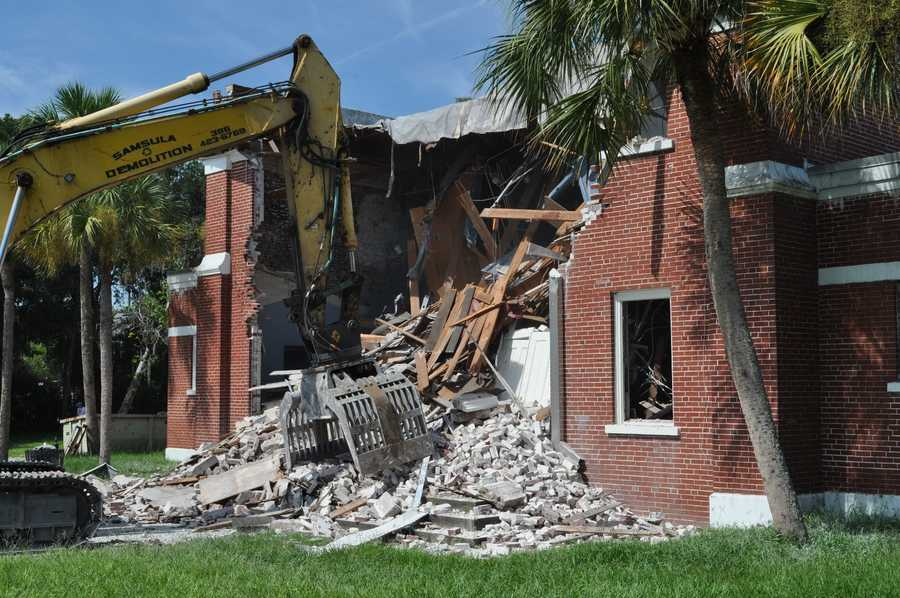 The 83-year-old building began to come down with the help of a big track hoe going in almost through the front door.The university decided the aging facility would be too costly to repair for today's students.