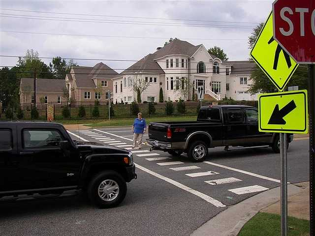 12. When approaching a crosswalk, and a car in the lane next to you is stopped, but you don't see a pedestrian in the crosswalk, what should you do?