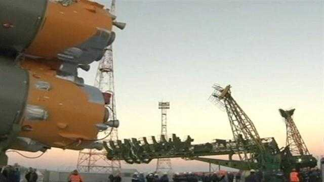 Russia has rolled out a towering Soyuz rocket to launch an American and two Russians to the International Space Station.