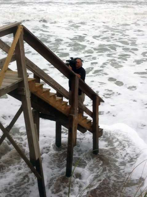 WESH 2 photographer Dave Goldschlag braves a washed-out stairway to shoot beach erosion at Melbourne Beach.