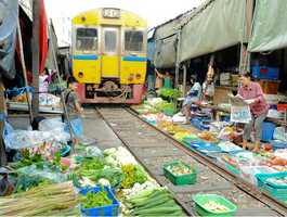 Market Railway- The Maeklong Market Railway in Thailand runs right through the heart of the market, forcing the vendors to pull back their awnings and move their produce out of the way when the train comes along