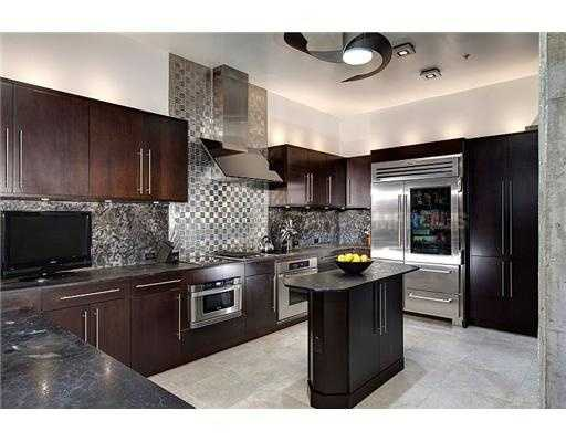 Dark wooden cabinets, marble wall and state-of-the-art chrome kitchen appliances.
