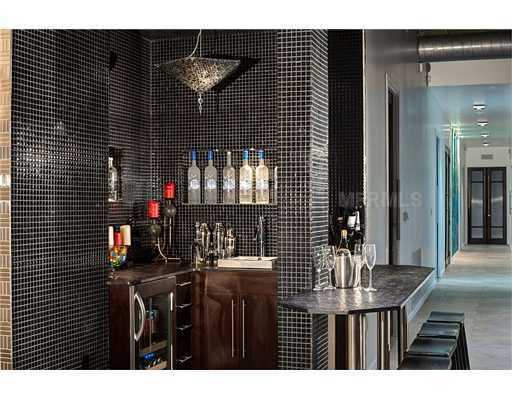 The black-tiled wet bar corner is tucked away for privacy.