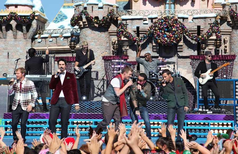 Backstreet Boys perform in front of Sleeping Beauty Castle.
