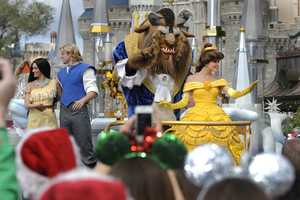 """Characters from Disney's classic animated films """"Pocahontas"""" and """"Beauty and the Beast"""" wave to the crowd Dec. 1, 2012."""