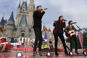 """Grammy Award-winning group Lady Antebellum poses in front of Cinderella Castle while taping the """"Disney Parks Christmas Day Parade"""" TV special in the Magic Kingdom park at Walt Disney World in Lake Buena Vista, Fla."""