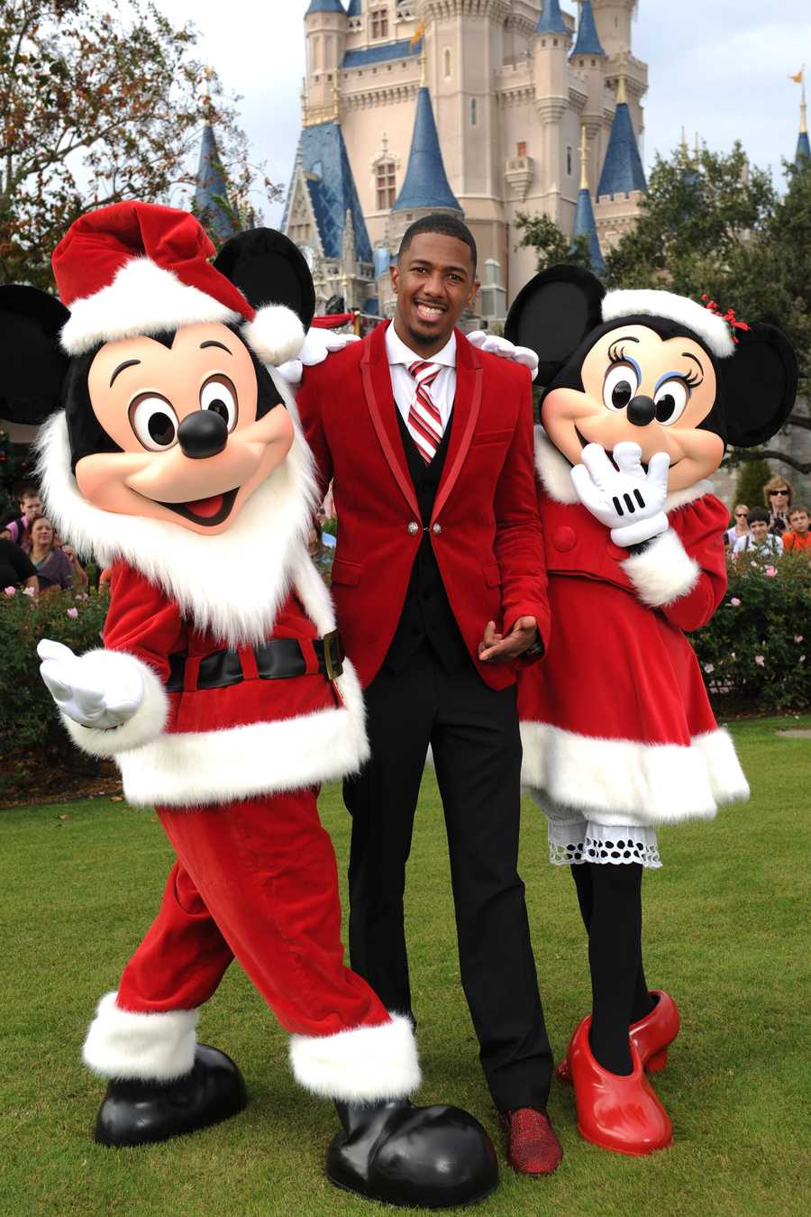 """Actor Nick Cannon points to his red sparkling holiday shoes as he poses with Mickey Mouse and Minnie Mouse while taping the """"Disney Parks Christmas Day Parade"""" TV special in the Magic Kingdom park at Walt Disney World in Lake Buena Vista, Fla. Cannon is one of the hosts for the holiday special."""