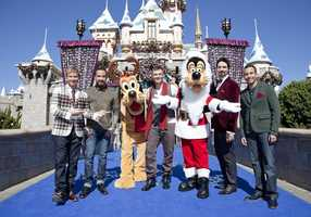 """Backstreet Boys pose with Santa Goofy and Pluto in front of Sleeping Beauty Castle at Disneyland Park in Anaheim, Calif. during a break in taping of the """"2012 Disney Parks Christmas Day Parade"""" TV special. The multi-platinum-selling pop group is one of the featured performers for the annual Disney holiday telecast, which airs on ABC on Christmas Day."""