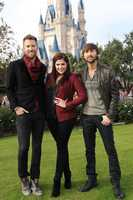 """Grammy Award-winning group Lady Antebellum poses in front of Cinderella Castle while taping the """"Disney Parks Christmas Day Parade"""" special in the Magic Kingdom park at Walt Disney World in Lake Buena Vista, Fla. The group headlines the telecast and performs a song from their new holiday album, """"On The Winter's Night."""""""
